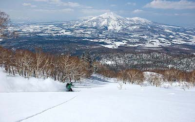 A skiers skiing down Mt Yohtei with Mt Niseko Annupuri forming a splendid backdrop